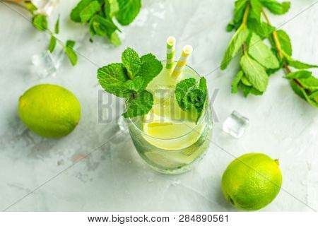 Mojito Cocktail With Lime And Mint In Highball Glass On A Gray And Green Concrete Stone Surface Back