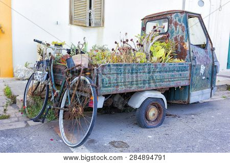Old disused motorbike used as a planter in the streets of Gallipoli, South Italy. poster