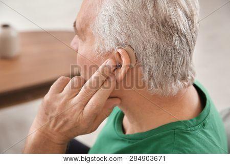 Mature Man Adjusting Hearing Aid At Home, Closeup