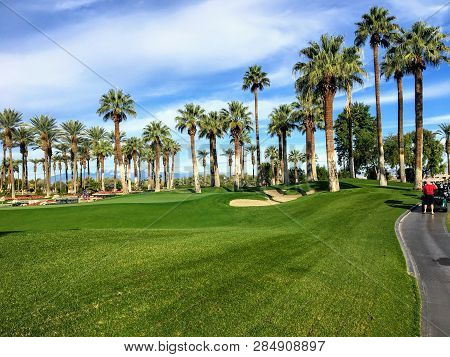 A Young Man Walking Towards The Green On A Par 4 Surrounded Palm Trees In The Background On The Dese