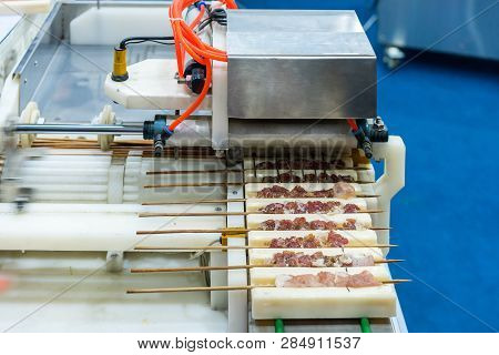 Close up asia barbecued or pork stick on support rail of automatic prick or stab pork machine for industrial manufacturing poster