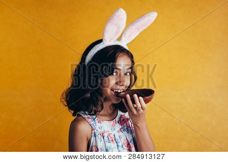 Cute Little Child Wearing Bunny Ears On Easter Day On Color Background. Girl Eating Chocolate Easter
