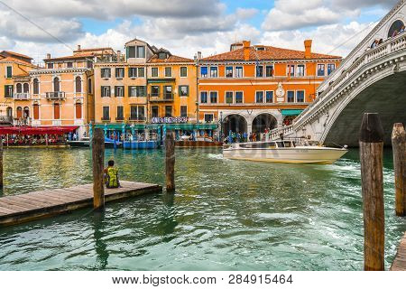 Venice, Italy - September 18 2018: A Man With A Backpack Sits On A Dock, As Tourists Enjoy Canal Fro