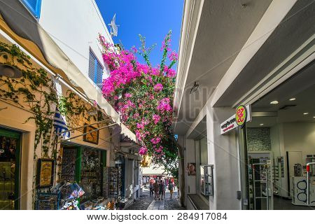 Santorini, Greece - September 16 2018: A Colorful, Narrow Street With Souvenir Shops And Pink Bloome