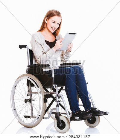 Woman sitting in wheelchair is holding tablet. Disabled life and work.