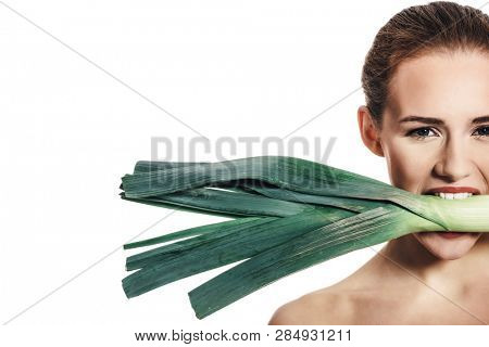 Vegetarian woman is holding a raw leek in her mouth. Copy space.