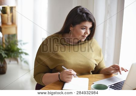 Indoor Shot Of Overweight Plus Size Beautiful Young Brunette Lady In Stylish Clothes Sitting At Desk