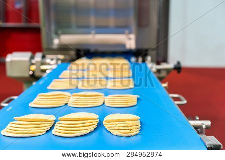 Close up bologna sliced plate on conveyor of automatic slicer machine for industrial food manufacture poster