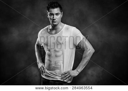 Handsome Muscular Man Posing In Wet Shirt, Looking At Camera.