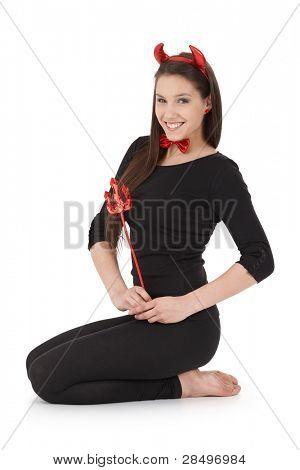Junge attraktive Frau kniend am Boden, Teufel Kostüm, das glücklich lächelnd tragen.?
