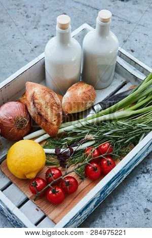 wooden box with fresh produce, fresh bread and olive oil
