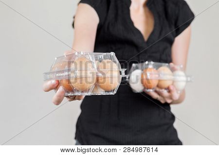 Caucasian Woman With Black Shirt Holding Two Plastic Egg Boxes Full Of Hen Eggs.