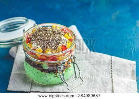 Chia Seed Pudding With Matcha Green Tea, Orange And Granola In Glass On Dark Blue Concrete Backgroun