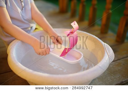 Cute Little Boy Playing With Homemade Ship In Basin Of Water On The Porch Of House. Kids Play. Imagi