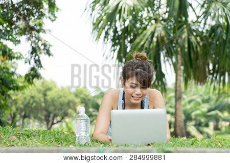 Happy Young Woman Using Laptop In The Park Lying On The Green Grass. Leisure Time Activity Concept.