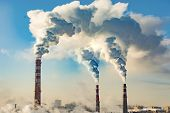 Industrial smokestacks against the blue sky . The concept of environmental pollution . poster