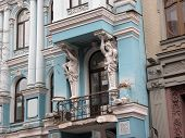 Two white cariatids ornated balcony of ancient blue mansion Kiev poster