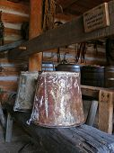 Old rusty buckets sit atop a workbench in a historic 1800s barn showing everyday life from the era poster