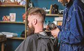 Barbershop concept. Hipster bearded client got hairstyle. Barber with hairdryer blows off hair out of cape. Barber with hairdryer works on hairstyle for bearded man, barbershop background poster