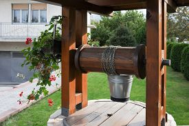 Stone Well With A Wooden Roof And A Bucket Of Water In Beautifully Modern Garden