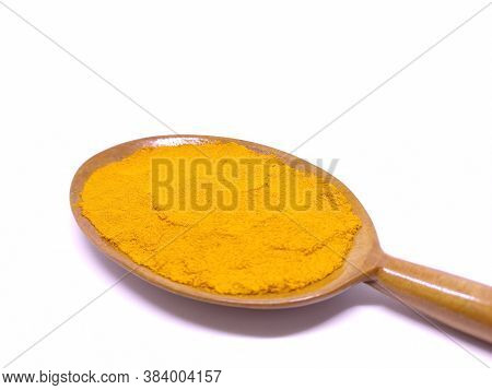 Turmeric Powder In A Wooden Spoon Lay Flat Isolated Over White Background. Concept Of Ayurvedic Medi