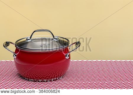 Steel Red Saucepan With Lid On Light Background, Motley Napkin On Table.