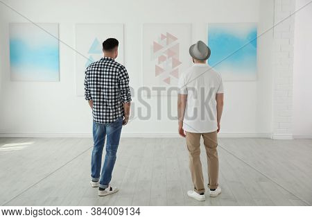 Men At Exhibition In Art Gallery, Back View