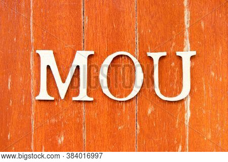 Alphabet Letter In Word Mou (abbreviation Of Memorandum Of Understanding) On Old Red Color Wood Plat