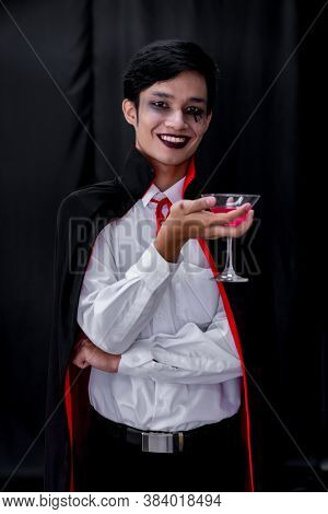 Portrait of asian young adult teenage man wear Halloween costume cloth hold glass of cocktail for Halloween party background. Halloween celebrate and international holiday concept.