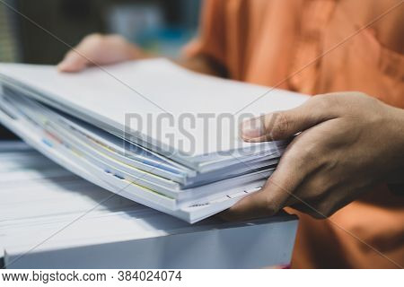 Office Workers Employee Holding Stacks Of Lot Documents Report Papers Waiting Be Managed On Desk In