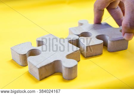 Jigsaw Puzzle Pieces For Teamwork On Yellow Paper Background, Teamwork Put Pieces Together To Connec
