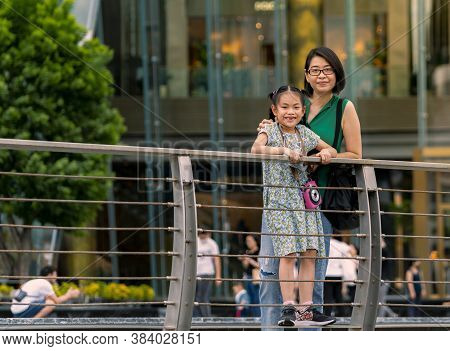 Asian Tourists Mother And Little Daughter Happy Together In Front Of Shopping Mall In Thailand, Blur