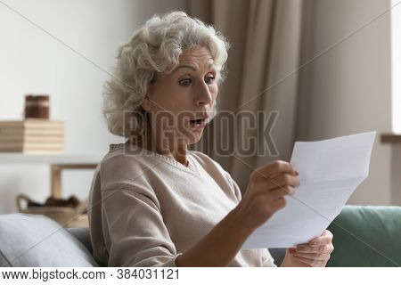 Amazed Shocked Mature Woman With Open Mouth Reading Letter