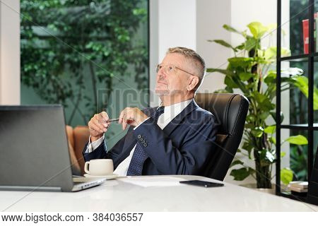 Smiling Dreamy Senior Businessman Sitting At Office Desk And Pondering Over Ideas For Business Devel