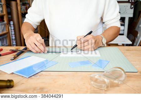 Faceless Female Entrepreneur Cutting Glass In Artisan Workroom. Business Woman Draws Line