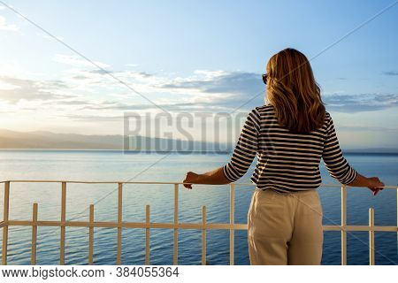 Shot Of Pretty Woman Wearing Straw Hat And Sunglasses While Standing On Balcony And Looking At Sea V