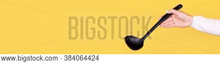 Black Plasic Ladle In Hand, Isolated On Yellow Background, Copy Space Template, Banner.