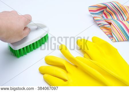 Yellow Rubber Gloves, Microfiber Wipe Lying On White Surface And A Hand Cleaning It With A Brush, Ho