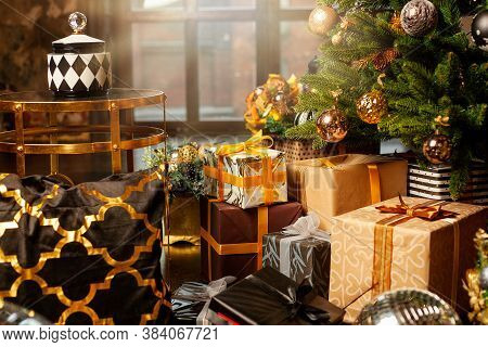 Christmas Tree Decorated With Gold Balls. Under The Christmas Tree A Large Number Of Christmas Gifts