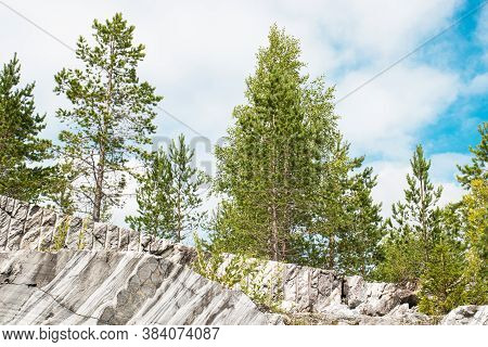 Marble Quarry, Marble Rocks In The Wild. Natural Stone. Trees On A Marble Rock. Ruskeala Mountain Pa
