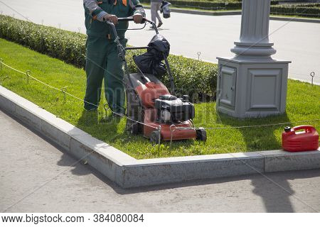 A Service Worker Mows The Lawn With A Lawn Mower.