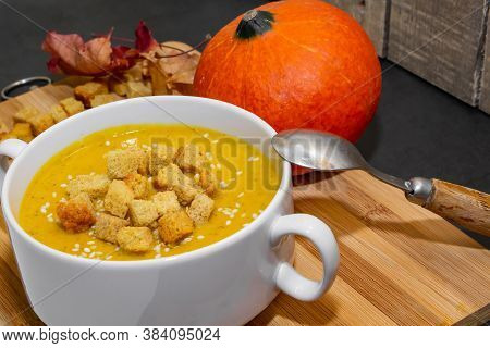 Autumn Pumpkin Soup With Sesame Seeds On A Wooden Background. Autumn Pumpkin Dish - Soup With Cracke
