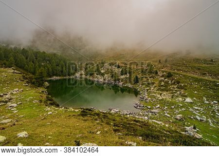 Mountain Pond Reflects The Surrounding Nature Shrouded In Morning Fog, Natural Landscape With Small