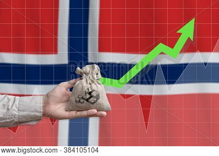 The Concept Of Economic Growth In Kingdom Of Norway. Hand Holds A Bag With Money And An Upward Arrow