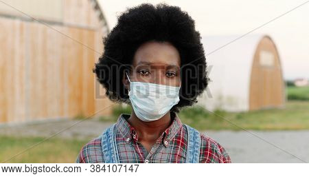 Close Up Of Young African American Sad Woman With Curly Hair And In Motley Shirt Outdoors Looking At