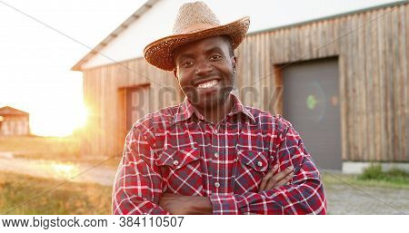 Young Handsome African American Man Farmer In Hat Standing And Smiling With Shed On Background. Port