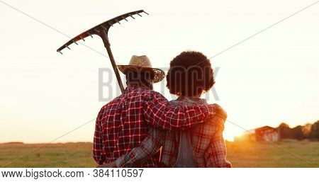Rear On African American Couple Of Farmers Walking In Countryside With Pitchfork Outside And Hugging
