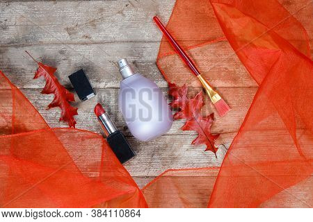 Perfume Bottle Lavender-colored,lipstick,bruch Lies Beautifully On A Wooden Background With Orange T