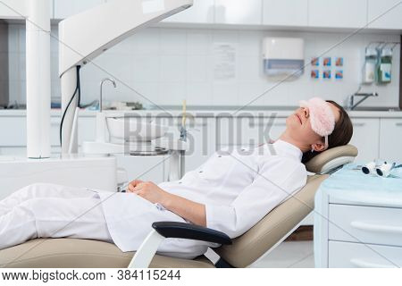 A Young Woman, A Dentist Or An Intern, Rests On The Chair In The Dentists Office In A Very Relaxed P