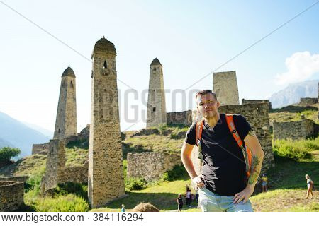 Young Man With Backpack Standing On Stone Near Old Towers On Background Of Mighty Mountains. Male To